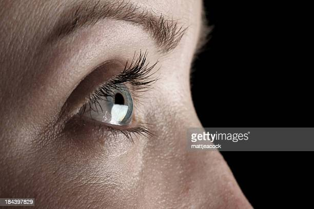 closeup side view of a woman's blue eye on black background. - eye black stock photos and pictures
