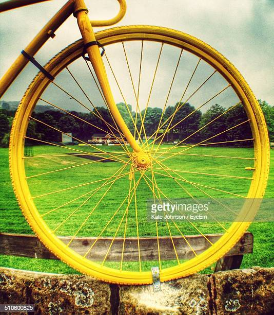 close-up side view of large yellow wheel statue against field - johnson stockfoto's en -beelden