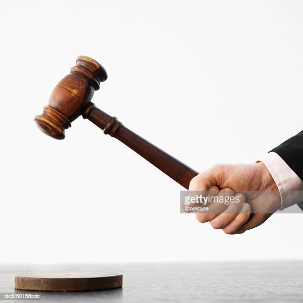 Close-up side view of male judge's hand banging gavel