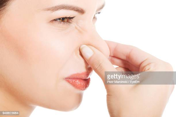 close-up side view of mid adult woman holding nose against white background - olor desagradable fotografías e imágenes de stock