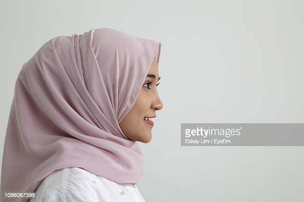 close-up side view of smiling young woman against white background - 宗教的なベール ストックフォトと画像