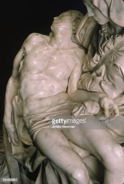 A closeup side view of the marble Pieta sculpture by Michelangelo created circa 1498 depicting Mary holding the dead body of Jesus Christ and located...