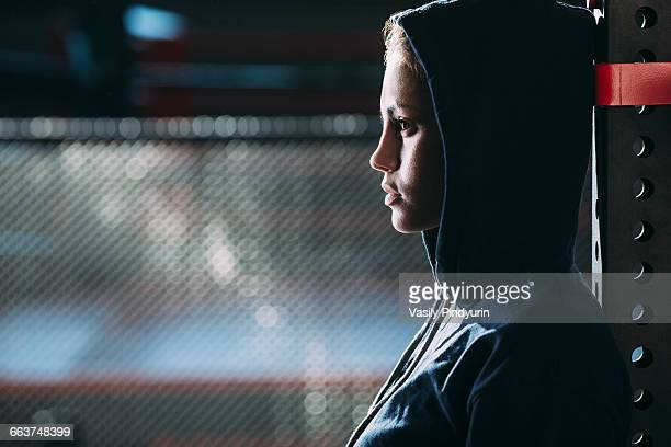 close-up side view of woman wearing hooded shirt standing at gym - capucha fotografías e imágenes de stock