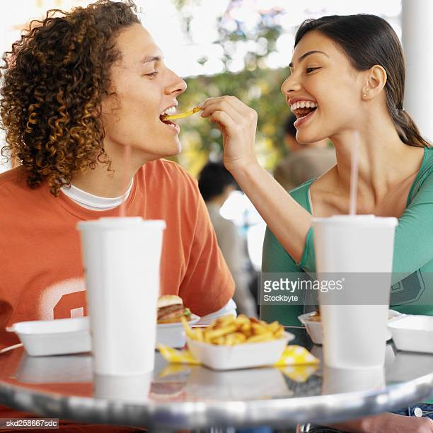 Close-up side view of young couple feeding each other in fast food restaurant