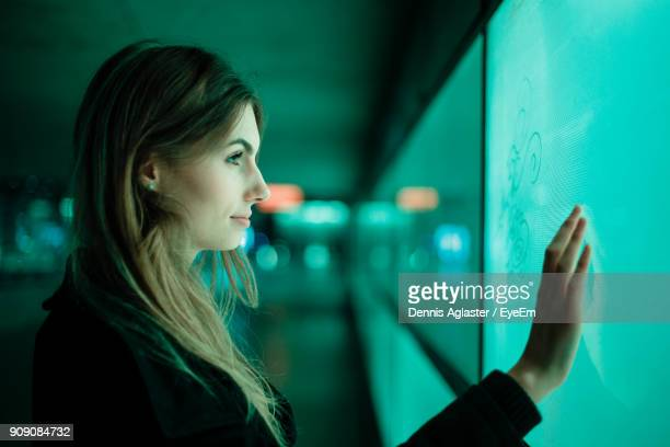 close-up side view of young woman against green wall - touch sensitive stock pictures, royalty-free photos & images