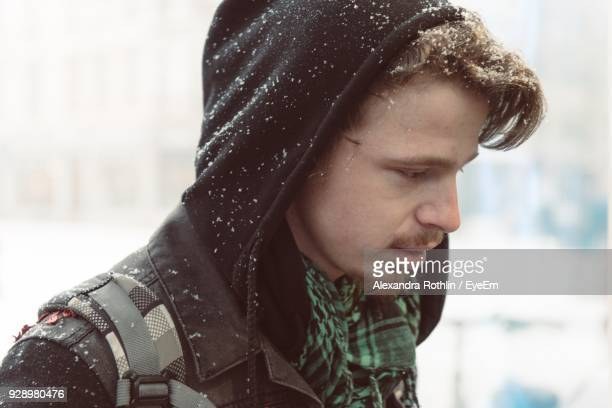 Close-Up Side View Of Young Woman With Snow On Hood