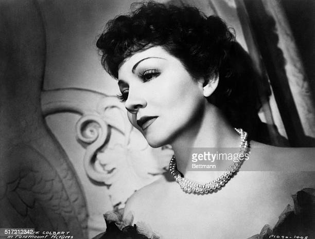 Closeup side view portrait of the beautiful Paramount Picture actress, Claudette Colbert. Head and shoulder photo with her head leaning against a...