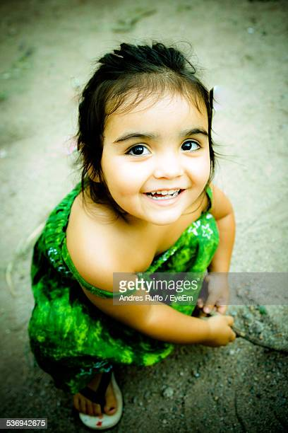 close-up smiling little girl crouching on ground - andres ruffo fotografías e imágenes de stock