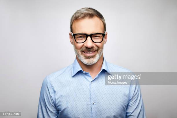 close-up smiling male leader wearing eyeglasses - männer stock-fotos und bilder