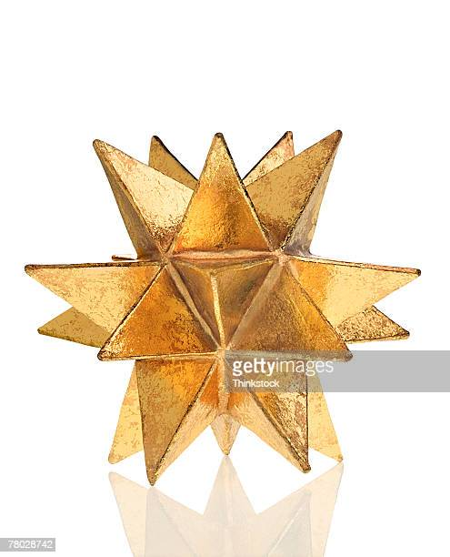 close-up still life of a gold moravian star on a white surface. - white gold stock pictures, royalty-free photos & images