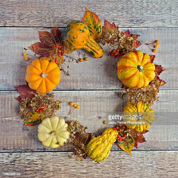 Close-up still-life flatlay image of Autumn Pumpkins and Gourds arranged on a wooden surface in the shape of a circular wreath
