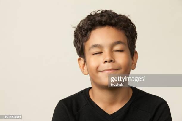 retrato do estúdio do close up de um menino dos anos de idade 12 em um fundo bege - olhos fechados - fotografias e filmes do acervo