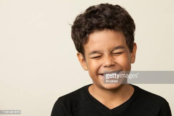 close-up studio portret van een 12-jarige jongen op een beige achtergrond - 12 13 jaar stockfoto's en -beelden