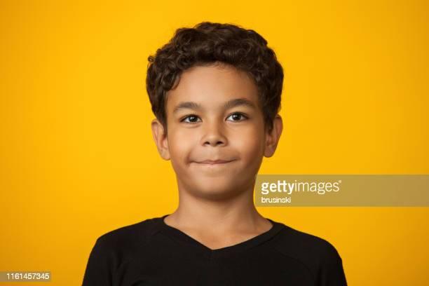 close-up studio portret van een 12-jarige jongen op een gele achtergrond - 12 13 jaar stockfoto's en -beelden