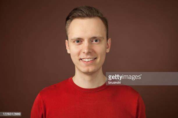 close-up studio portrait of a 24 year old man - red shirt stock pictures, royalty-free photos & images