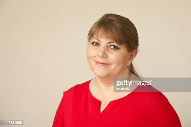 close-up studio portrait of a 45 year old woman - beige background stock pictures, royalty-free photos & images