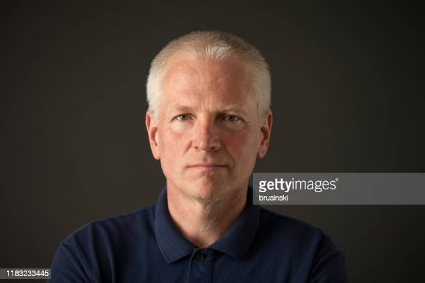 黒い背景に青いポロシャツを着た55歳の白髪男性のクローズアップスタジオの肖像画 - ピンクの頬 ストックフォトと画像