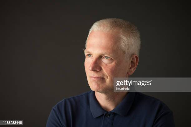 close-up studio portrait of a 55 year old gray-haired man in a blue polo shirt on a black background - three quarter front view stock pictures, royalty-free photos & images