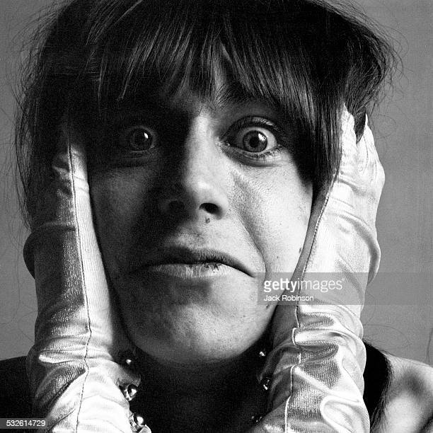 Close-up studio portrait of American rock singer Iggy Pop, of the group the Stooges, as he poses in satin gloves with his hands on either side of his...