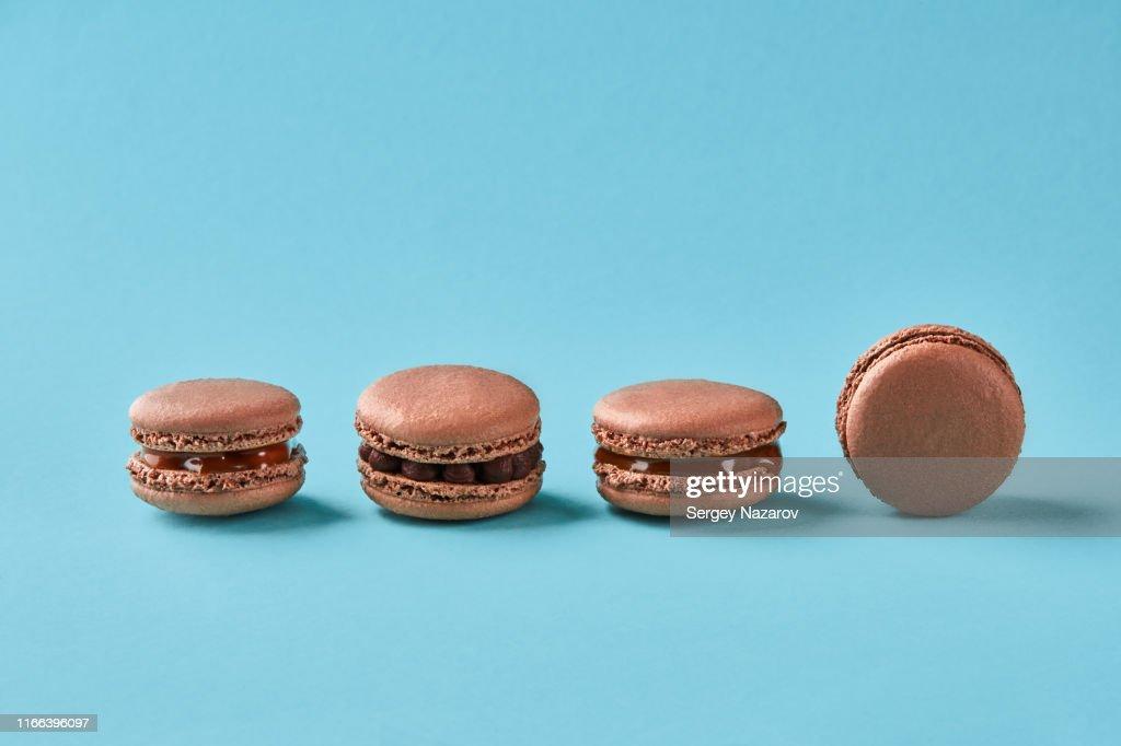 Close-up studio shot of tasty chocolate macarons on blue background : Stock Photo
