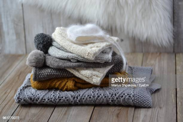 Close-Up Sweaters Folded On Wooden Table