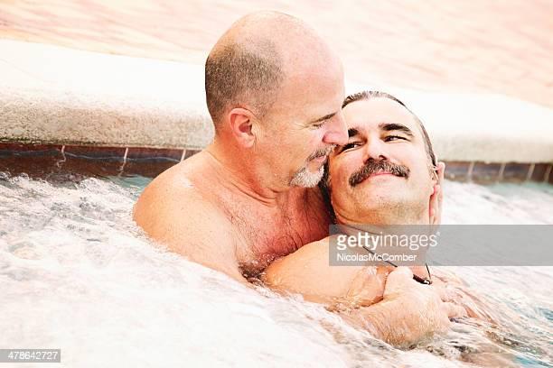 Close-up two mature gay bear men embracing in hot tub