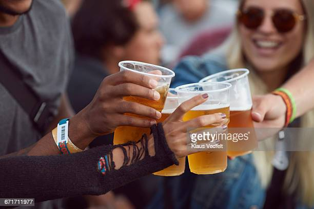 close-up uf hands toasting in beer, at festival - disposable cup stock pictures, royalty-free photos & images