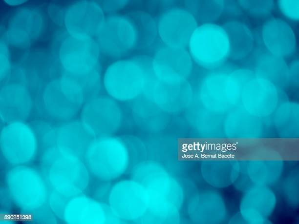 Close-up unfocused lights in the shape of circles of blue and turquoise background