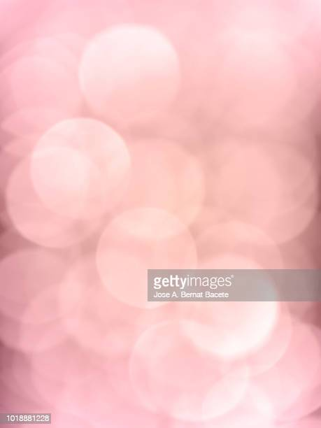 Close-up unfocused lights in the shape of circles of colors outdoors, wallpaper of light pale pink color. High resolution photography.