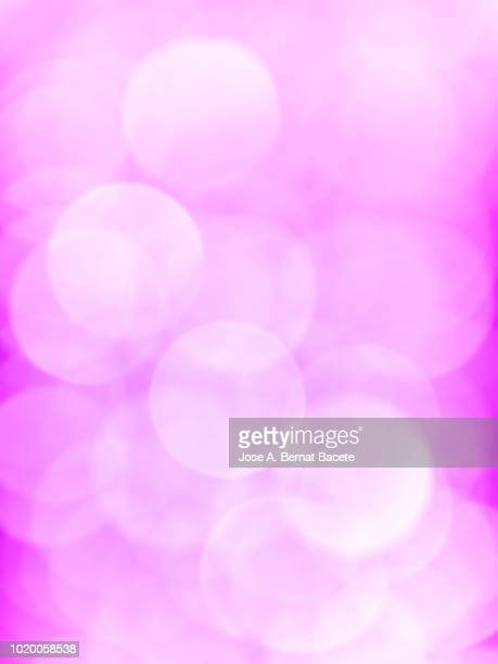 Close-up unfocused lights in the shape of circles of colors outdoors, wallpaper of light pink color. High resolution photography.