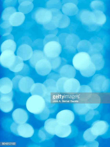 Close-up unfocused lights in the shape of circles of colors outdoors, wallpaper of blue and Light Blue colors. High resolution photography. Spain.