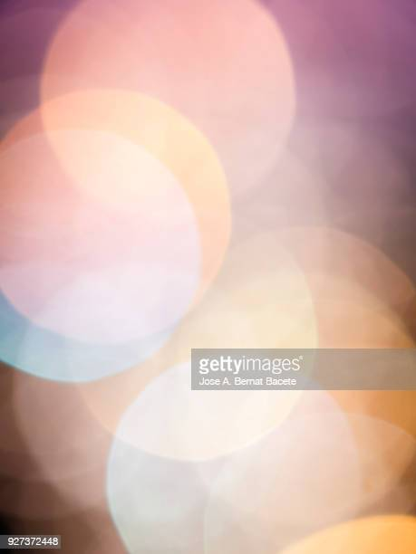 Close-up unfocused lights in the shape of circles of colors outdoors, wallpaper of light pink and orange colors. High resolution photography.