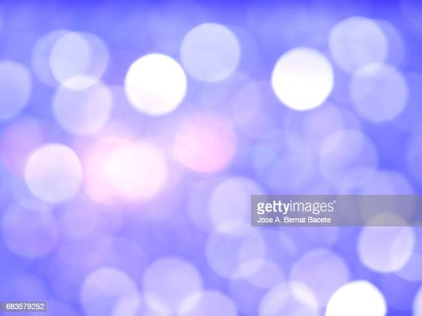 Close-up unfocused lights in the shape of circles of light blue background