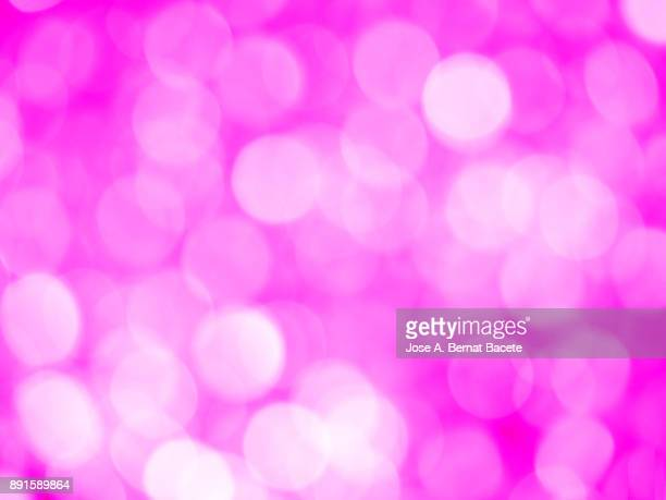 Close-up unfocused lights in the shape of circles of pink and  whithe background