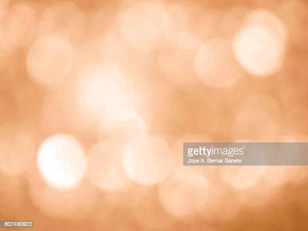 Close-up unfocused lights in the shape of circles of vintage orange background