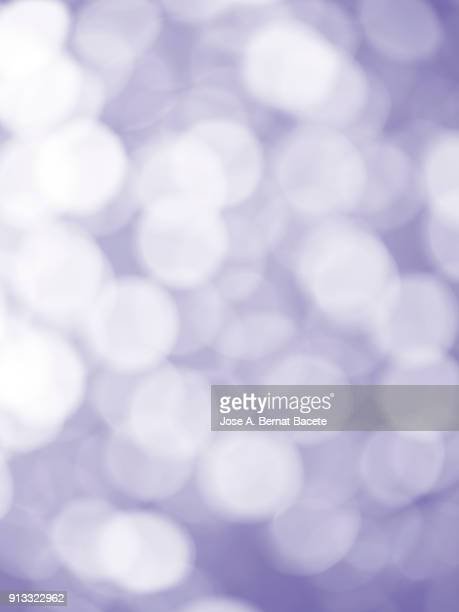 Close-up unfocused lights in the shape of circles of violet and white colors on a purple background