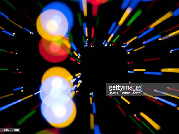 Close-up unfocused of lights of colors in the shape of circles and lines of colors blue, yellow and red on a black background.