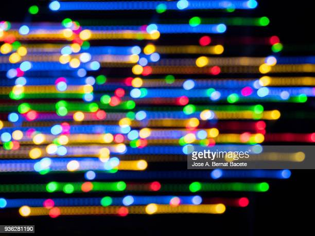 Close-up unfocused of lights of colors in the shape of circles and lines of colors blue, yellow and red on a black background. Spain.