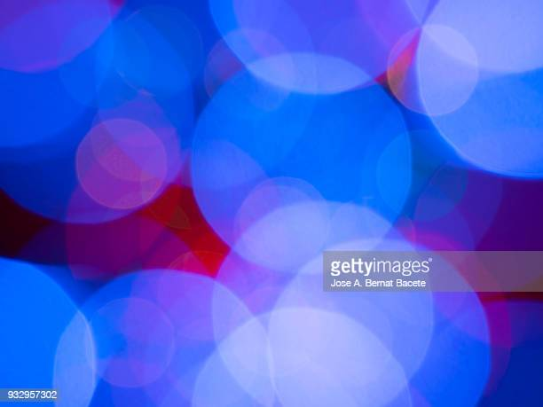 Close-up unfocused of lights of colors in the shape of circles of colors blue and purple on a black background. Spain.
