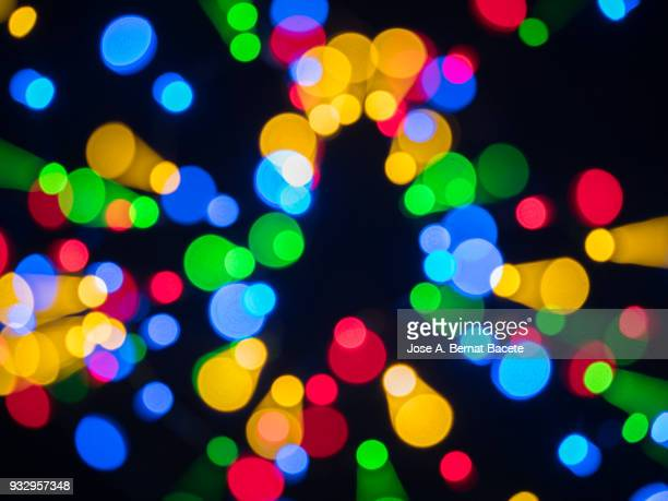 Close-up unfocused of lights of colors in the shape of circles of colors blue, yellow and red on a black background. Spain.
