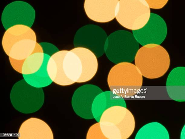 Close-up unfocused of lights of colors in the shape of circles of colors yellow and green on a black background. Spain.