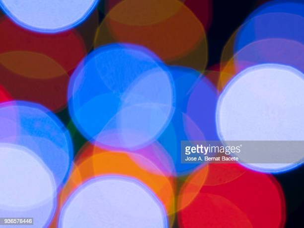 Close-up unfocused of lights of colors in the shape of circles of colors blue and red on a black background.