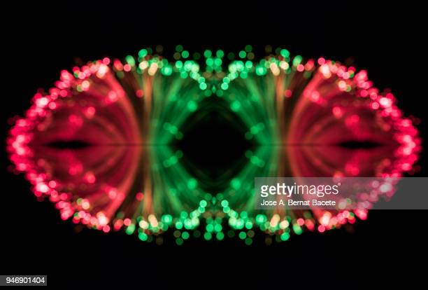 Close-up unfocused of lights of colors in the shape of circles of colors green and red on a black background.