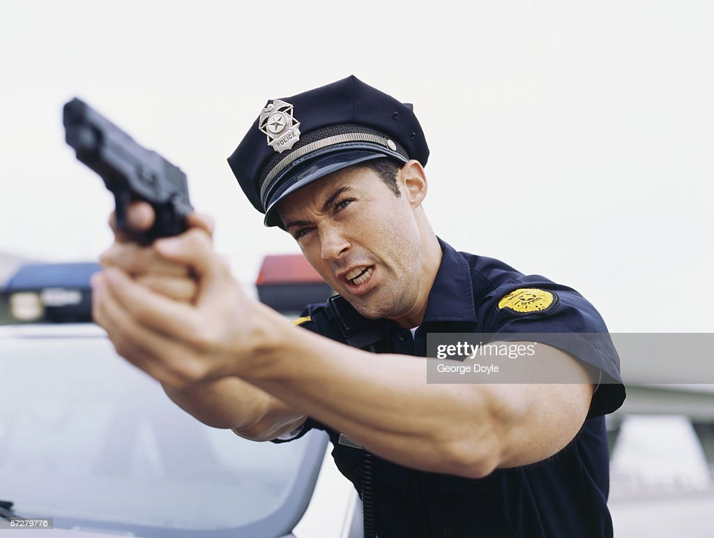 Close-up vie of a policeman holding a gun and screaming : Stock Photo