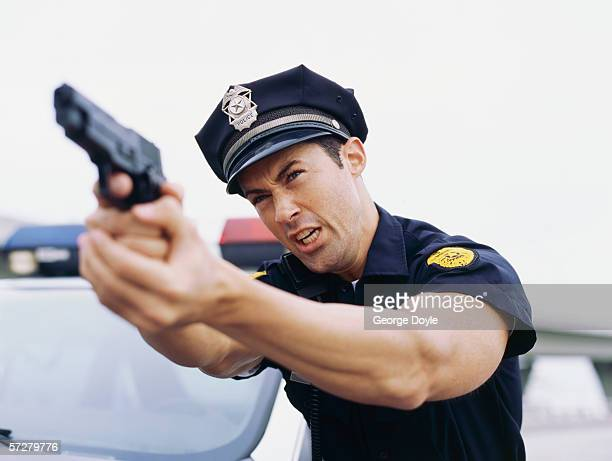 Close-up vie of a policeman holding a gun and screaming