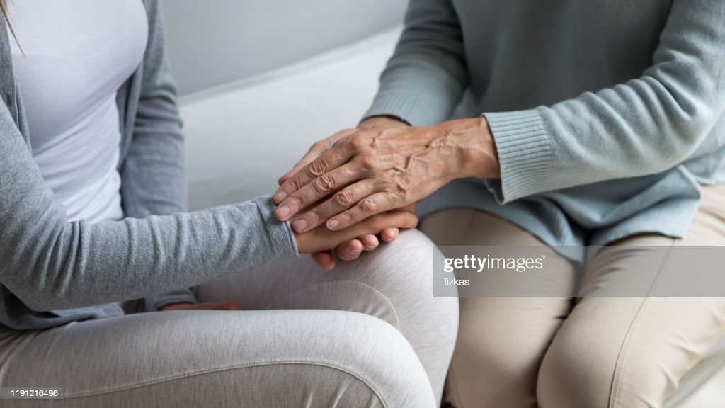 Closeup view mom stroking hands of adult grownup daughter : Stock Photo
