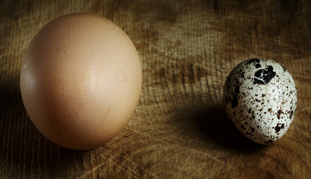Close-up view of a big and small eggs on a wooden surface