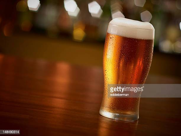 Closeup view of a clear pint of beer in a bar