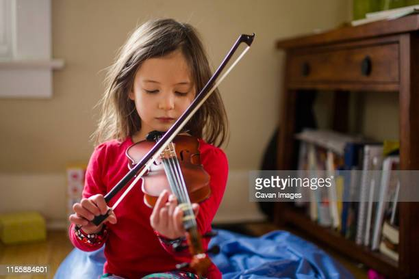 close-up view of a focused little girl practicing violin on floor - violin stock pictures, royalty-free photos & images