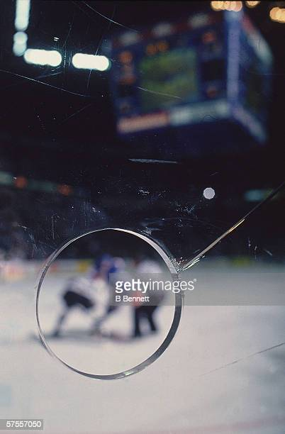Closeup view of a hole cut into the plexiglass barrier of an ice hockey rink 1980s The hole is there to allow photographers a clear view of the onice...